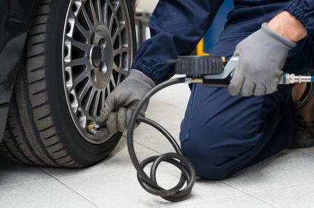 Gros plan d'un mécanicien à la station de service de réparation Vérification de la pression des pneus avec manomètre
