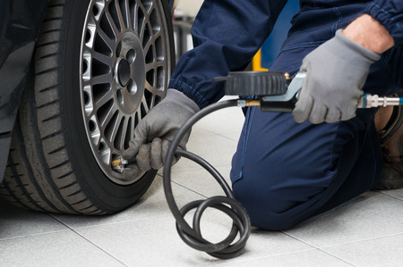 Closeup Of Mechanic At Repair Service Station Checking Tyre Pressure With Gauge Archivio Fotografico