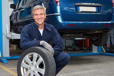 Portrait Of Happy Mature Mechanic At Repair Service Station Holding A Tyre Archivio Fotografico