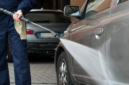 Close-up Van Een Monteur wassen van een auto Door Waterdruk bij Garage Stockfoto