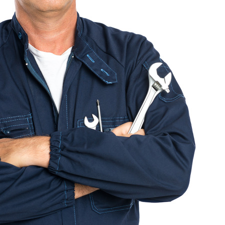 Closeup Of A Mechanic With Arm Crossed Holding Spanner Isolated On White Background Stockfoto
