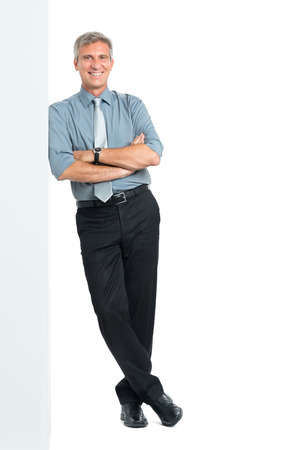 Happy Mature Manager With Arms Crossed Leaning Against Blank Placard Looking At Camera Isolated on White Background Stockfoto
