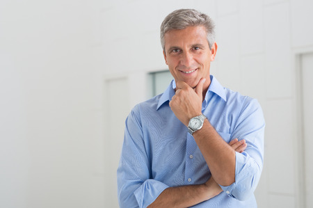 businessman smiling: Portrait Of Smiling Mature Businessman With Hand On Chin In His Office Stock Photo