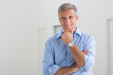 Portret van lachende volwassen zakenman met hand op kin in Zijn Bureau