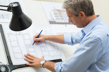 Portrait Of Male Architect Working On Blueprint At Office photo