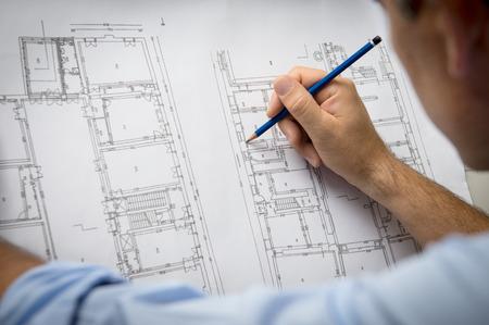 Close-up Van Mannelijke architect werkt aan blauwdruk op kantoor.