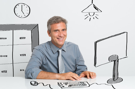 Portrait Of Happy Mature Businessman Sitting At Office Desk photo