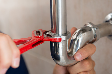Closeup Of Plumber Fixing Pipe With Wrench Banco de Imagens - 33251412