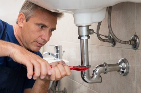Closeup Of Male Technician Fixing Sink Pipe In a Bathroom photo