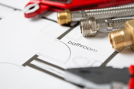 Closeup Of Wrench And Pipes On Bathroom Blueprint Stock Photo