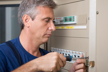 Closeup Of Electrician Repairing Circuit Breaker photo