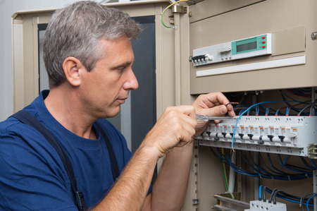 skilled labour: Repairman Fixing An Electric Switchboard Indoor Stock Photo