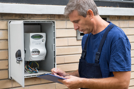 Portrait Of Electrician Worker Inspecting Electric Meter photo