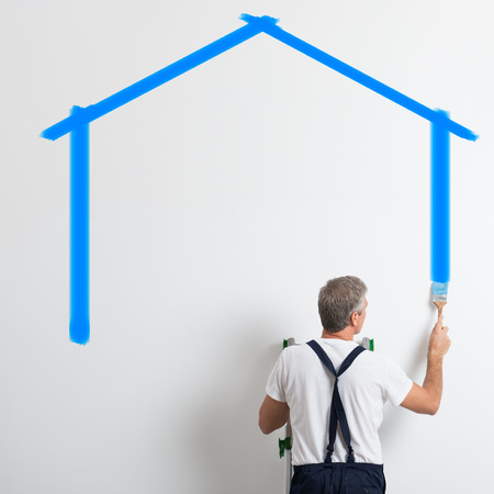 Painter On Stepladder Painting Wall With Brush In New House photo