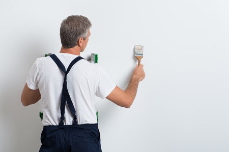 Painter On Stepladder Painting Wall With Brush photo