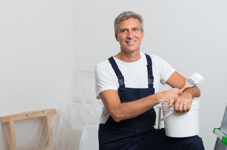 Portrait Of Happy Mature Painter With Stepladder And Paint Bucket