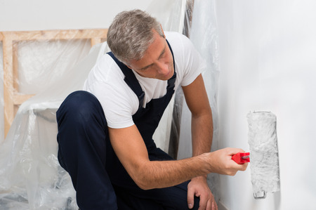 Portrait Of A Mature Man On Painting Wall With Roller