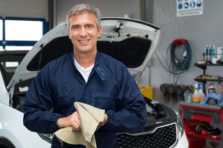 auto monteur: Portret van een gelukkige Automonteur reinigen van de handen met een doek Stockfoto
