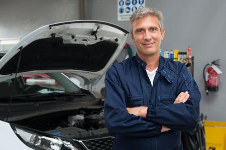 Portret Van Tevreden Automonteur Met Arm Gekruiste In Garage Stockfoto