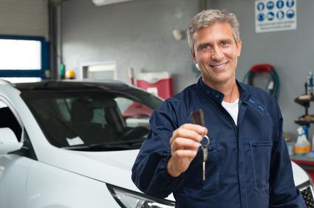車のキーを保持しているガレージに成熟した自動車整備士の肖像画