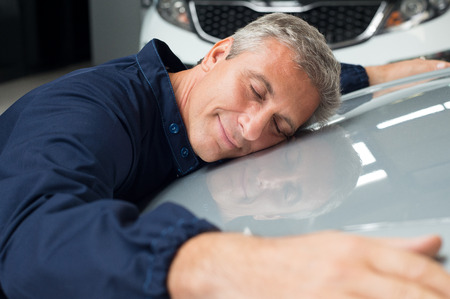 Closeup Of Mature Mechanic With Eyes Closed Lying On Car Bonnet Hugging photo