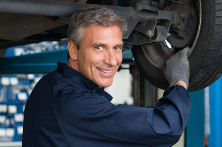mechanist: Portrait Of Happy Mature Mechanic At Repair Service Station Changing Tire Stock Photo