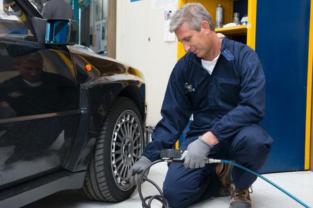 Retrato de Mecánico feliz maduros en la estación de servicio de reparación de Verificación de la presión de los neumáticos