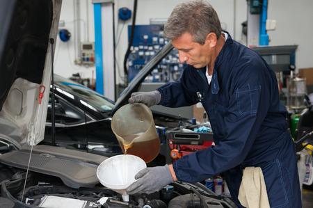 Mecánico Verter aceite en motor de coche en el taller Foto de archivo