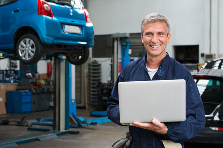 Portrait Of Happy Mature Mechanic At Repair Service Station With Laptop photo