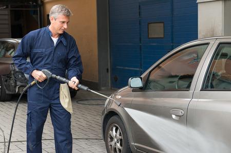 carwash: Primer plano de un hombre maduro que lava un coche por agua a presión En la estación de servicio