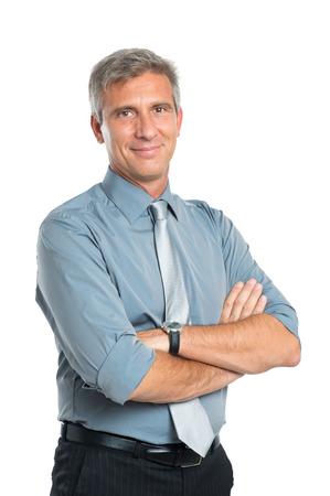 empresario: Retrato de la sonrisa confidente del hombre de negocios maduros con los brazos cruzados mirando a la c�mara aislada en fondo blanco