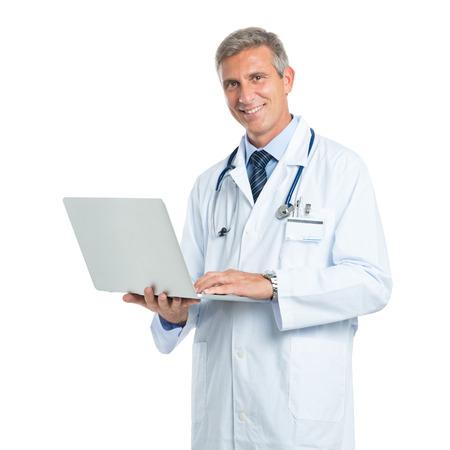 persona de pie: Feliz maduro doctor Holding Laptop Mirando a la cámara aislada en el fondo blanco Foto de archivo