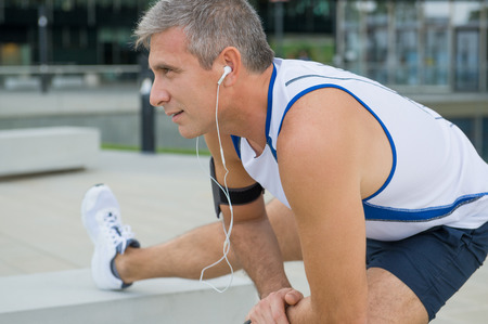 aerobic exercise: Mature Male Athlete Exercising And Listening To Music In The City