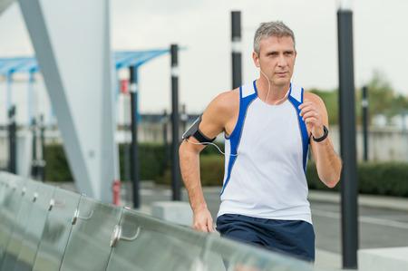 hombres corriendo: Hombre maduro Correr Y escucha la música en auriculares en la Ciudad