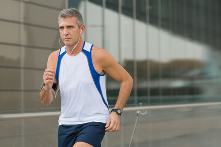Mature Man Jogging And Listening To Music On Earphones In The City Stok Fotoğraf