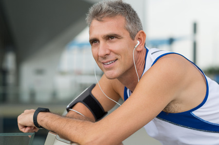 Portrait Of Happy Mature Man Listening Music On Earphones photo