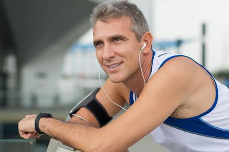 corriendo: Retrato de hombre maduro feliz escuchando m�sica en auriculares