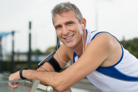 Portrait Of Happy Mature Man Enjoying Music On Earphones