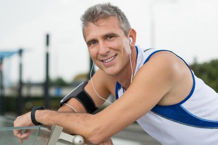 Portret van gelukkig volwassen man genieten van muziek op koptelefoon