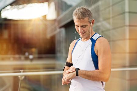 Portrait de l'heureux homme d'âge mûr avec cardiofréquencemètre poignet Banque d'images
