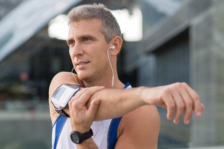 Rijpe Mannelijke Atleet Stretching en luisteren naar muziek buiten Stockfoto