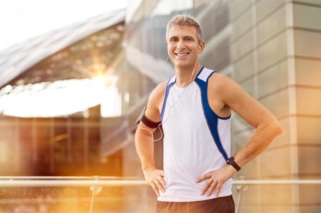 イヤホン屋外カメラ目線で幸せの成熟した男性のジョガーの肖像画
