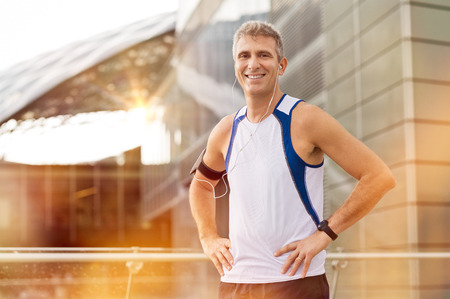 Portrait Of Happy Mature Male Jogger With Earphone Looking At Camera Outdoor