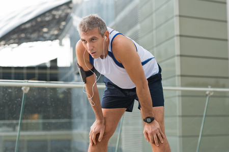 1 mature man: Portrait Of Exhausted Male Jogger Resting In A Urban Place