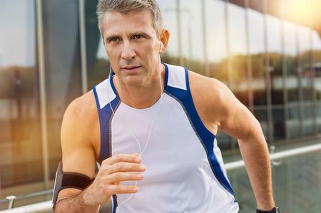 corriendo: Retrato de un hombre maduro atleta que activa con auriculares en una ciudad