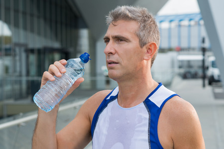 man drinking water: Athletic Man Drinking Water After Running Session In The City Stock Photo