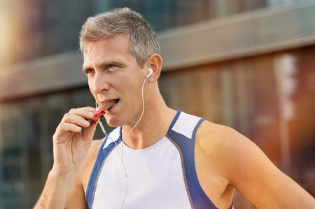 merenda: Ritratto Di Fitness uomo maturo mangiare una barretta energetica Di Cioccolato