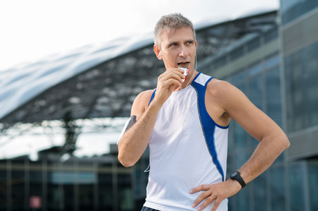 deportista: Atlético hombre maduro comer barra de chocolate y escuchar música en el casco urbano
