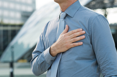 honestidad: Detalle de un empresario con mano en el pecho al aire libre