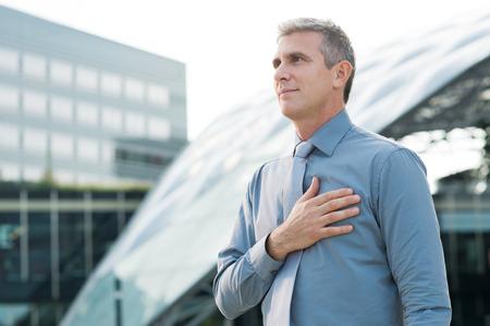 자신의 심장 옥외에 손을 맹세하는 성숙한 사업가의 초상